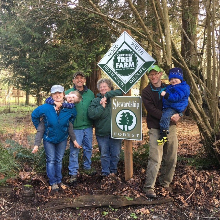 The New family: From left, daughter, Jenn Parker, grandson Tyler, Dave New, Dar New, Jeff Parker and grandson Alex Parker, by ATF and Stewardship signs. The New family was awarded the Tree Farmer of the Year award in 2018. (Photo by Tami Perrault)